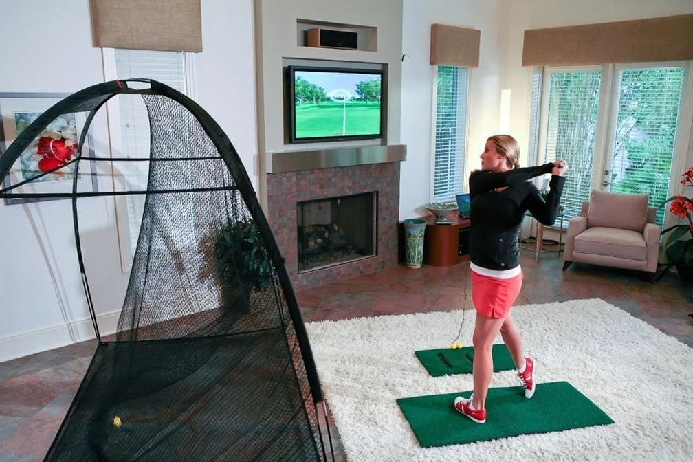 A woman using a golf simulator for home