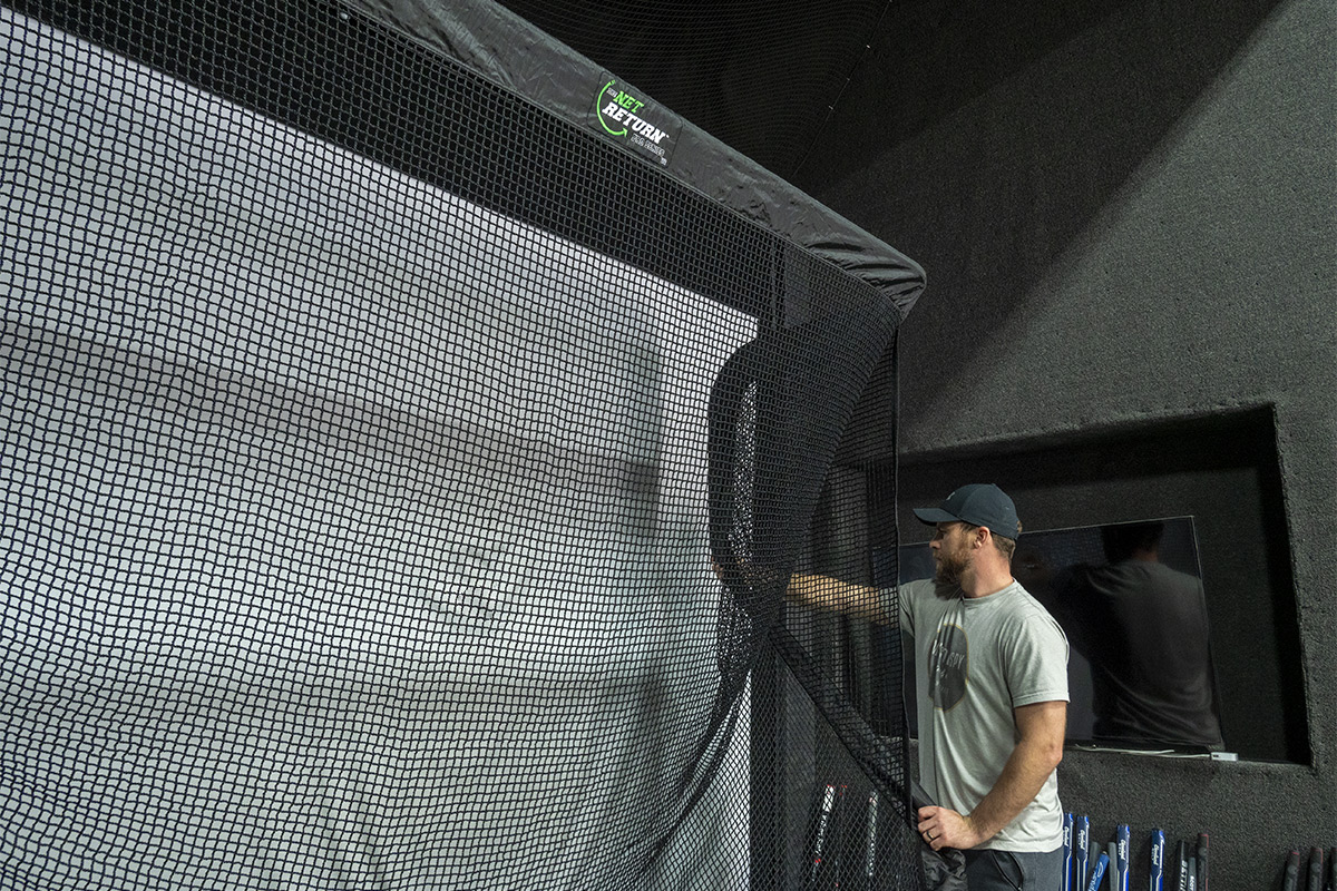 A man setting up one of the best golf nets inside