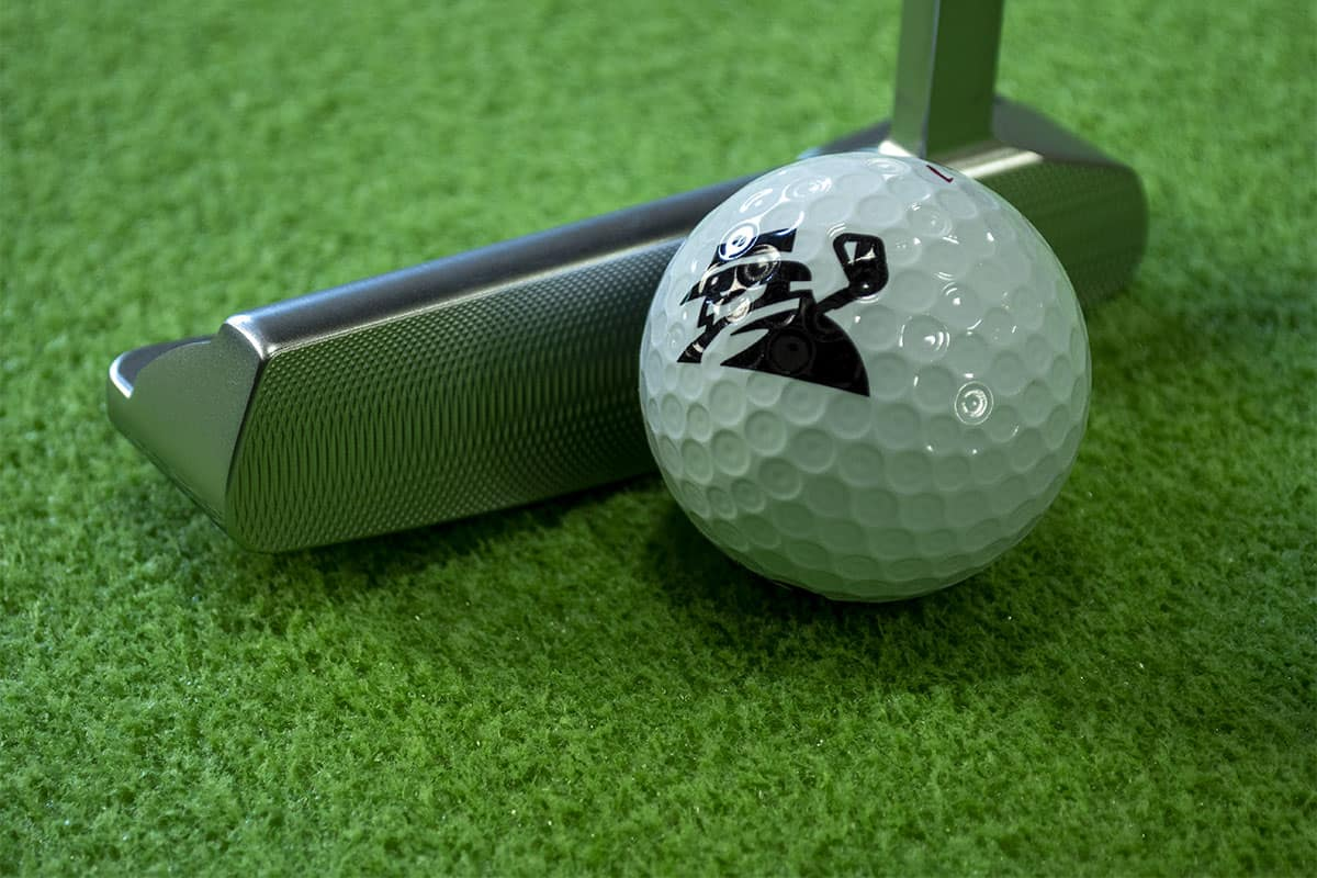 A ball and putter on one of the best indoor putting mats