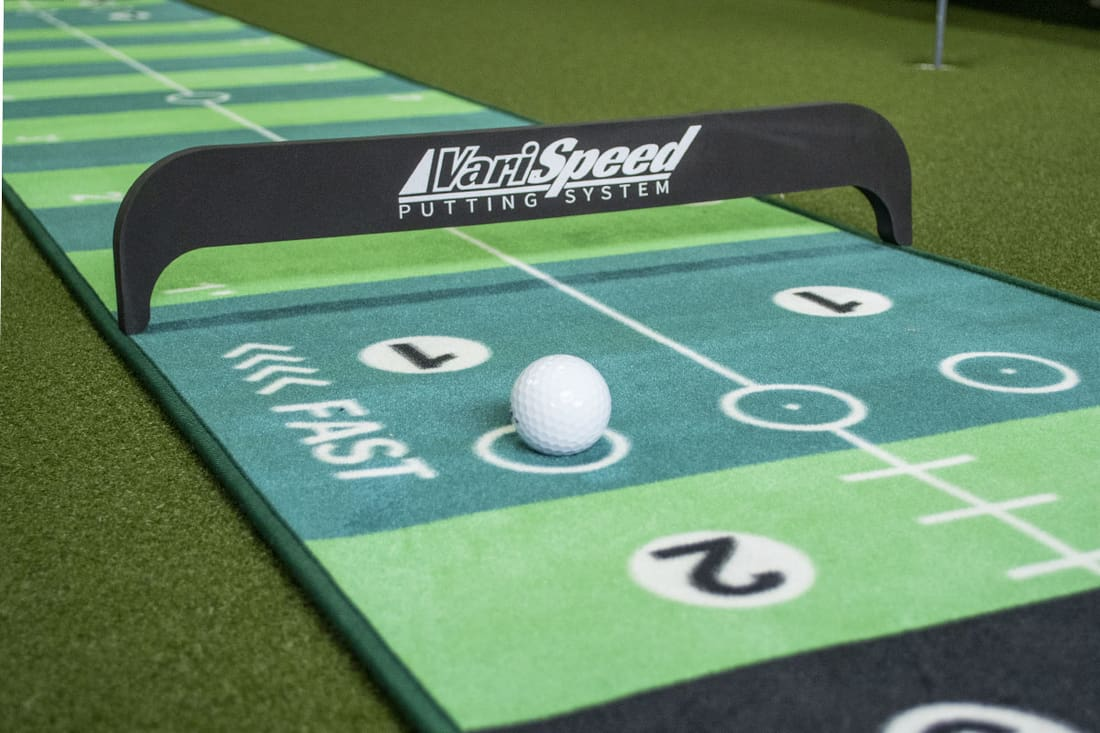 A golf ball on one of the best indoor putting mats that doubles as a shuffleboard