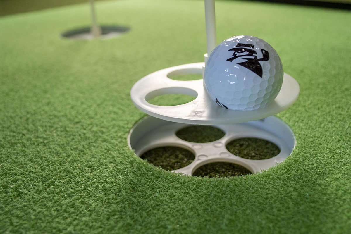 Pulling a ball out of a hole on one of the best indoor putting mats