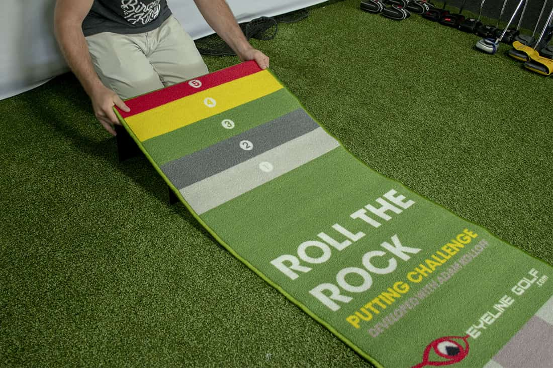 Someone rolling up one of the best indoor putting mats