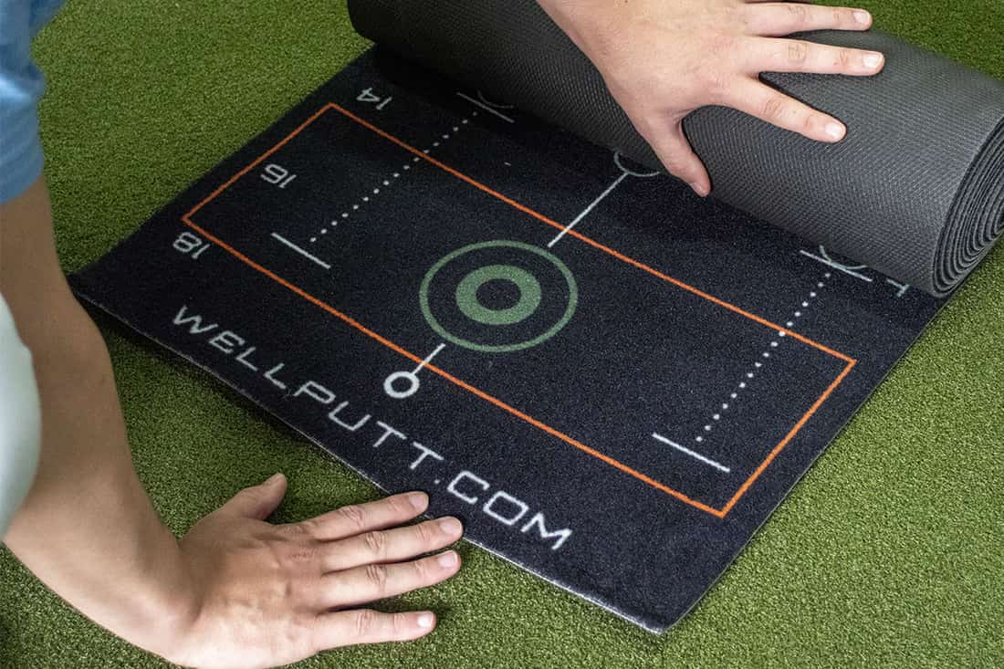 Someone unrolling one of the best indoor putting mats