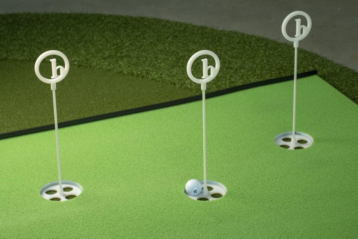 Three hole markers on one of the best indoor putting mats