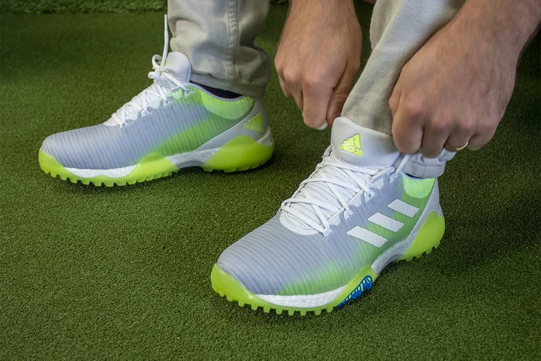 A person putting on Codechaos, some of the best spikeless golf shoes of 2020