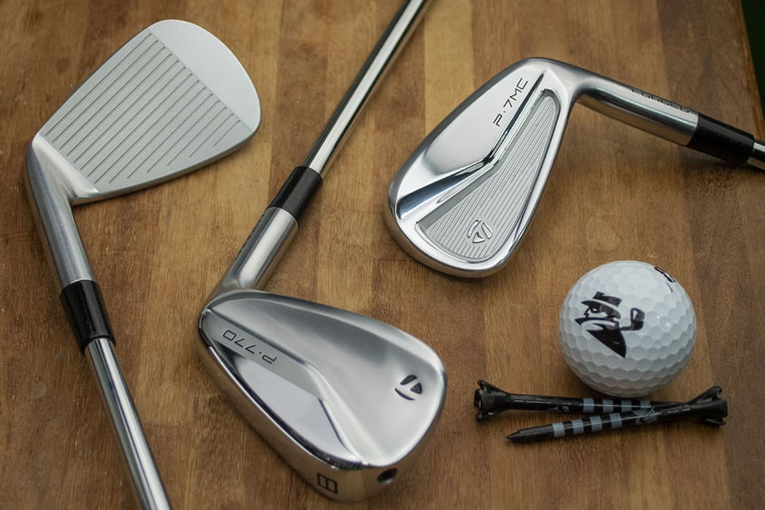 Three TaylorMade Irons on a table