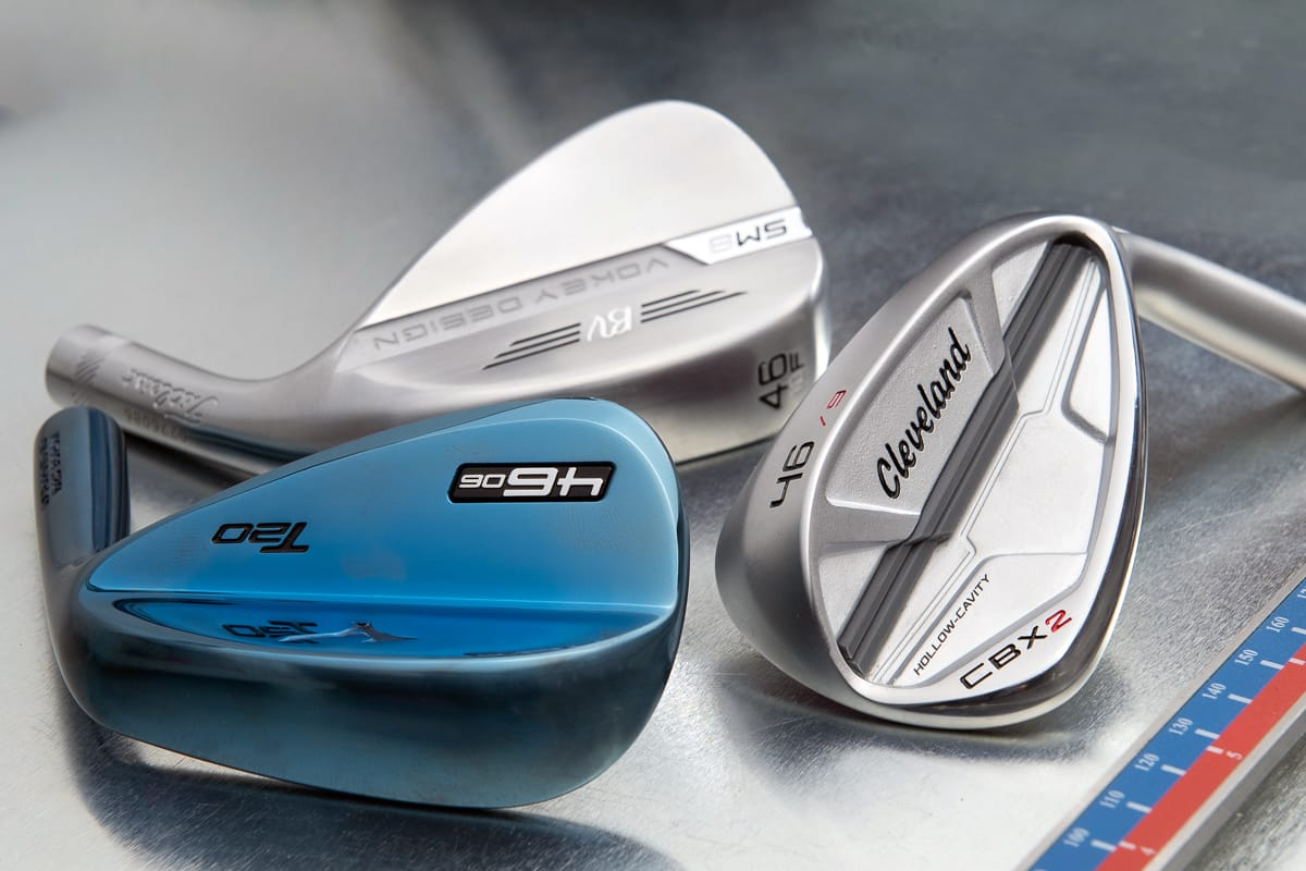 Three specialty pitching wedge heads on a table