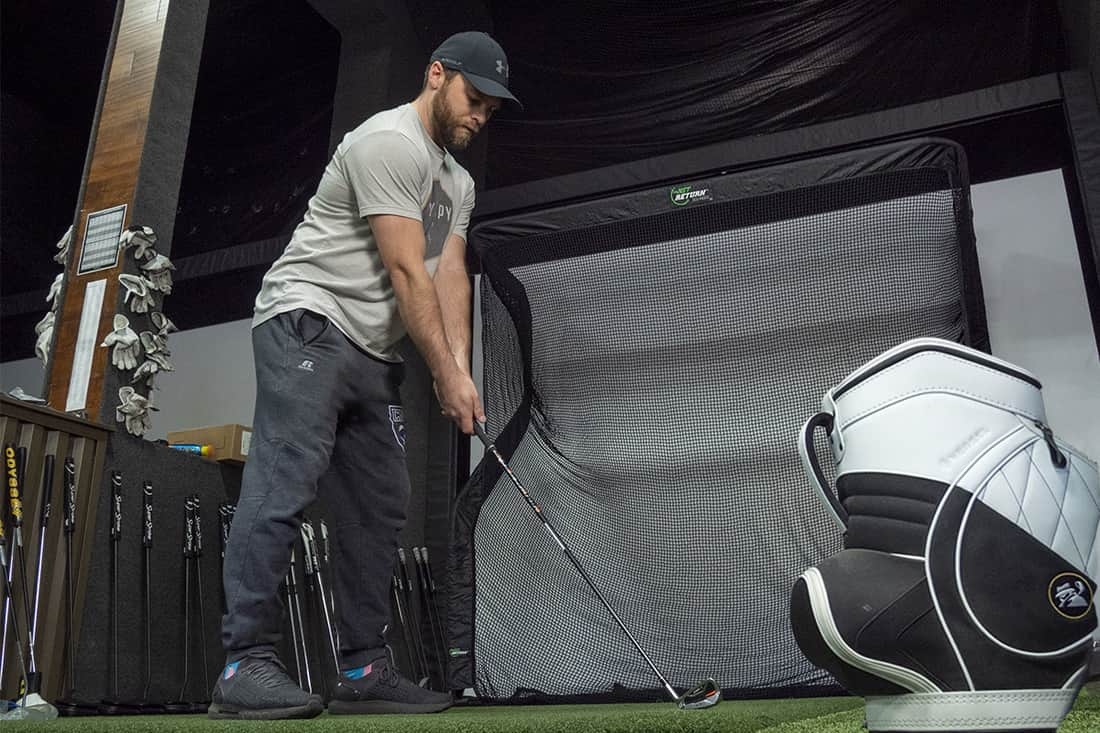 A man golfing into one of the best golf nets inside
